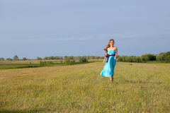 Beautiful girl stands on green field Stock Photo