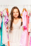 Beautiful girl stands among hangers with clothes Stock Images