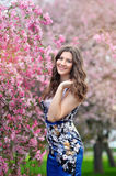 Beautiful girl stands in the lush spring garden Royalty Free Stock Photo
