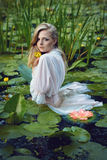 Beautiful girl stands in the middle of the pond with lotuses Stock Images