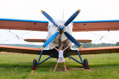 Beautiful girl stands near the airplane Royalty Free Stock Image