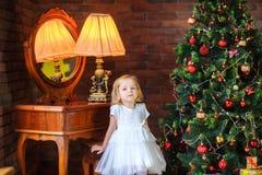 beautiful girl stands near a festive Christmas tree stock photos
