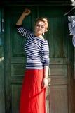 Beautiful girl stands near green grunge door Stock Images