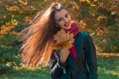Beautiful girl stands in the park with long developing hair and keeps the leaves Stock Photography