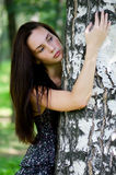 The beautiful girl stands a tree Stock Image