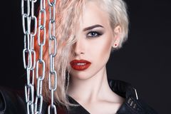 Beautiful girl with steel chain. Sexy blonde woman with curly hair and make up Royalty Free Stock Photo