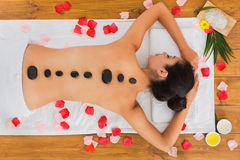Beautiful girl at stone massage spa in wellness center. Black marble stone massage in spa. Top view of beautiful girl with stones on back and rose petals in Royalty Free Stock Photo