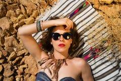 Beautiful girl on a stony beach. Beautiful hippie girl alone on a stoney beach Stock Image