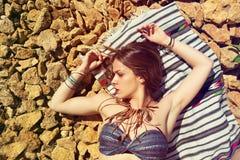 Beautiful girl on a stony beach. Beautiful hippie girl alone on a stoney beach Royalty Free Stock Photography
