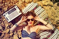 Beautiful girl on a stony beach. Beautiful hippie girl alone on a stoney beach. Retro toned image Stock Image
