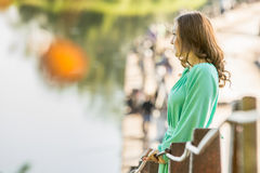 Beautiful girl stopped on the bridge over the river and looked into the distance Royalty Free Stock Photos