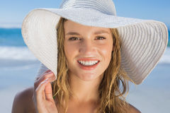 Beautiful girl in straw hat on the beach smiling at camera Stock Photography
