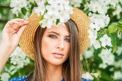 Posing in blooming garden. Beautiful girl in a straw hat posing in a blooming garden. Beauty, fashion royalty free stock image
