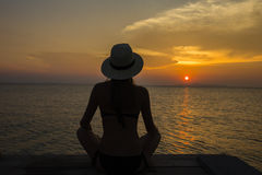 Beautiful girl in a straw hat sitting on the beach during sunset. Thailand Royalty Free Stock Photos