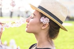 Beautiful girl in straw hat sniffs blossom branch. Of tree or bush outdoor stock photo