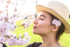 Beautiful girl in straw hat sniffs blossom branch. Of tree or bush outdoor royalty free stock image