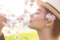 Beautiful girl in straw hat sniffs blossom branch. Of tree or bush outdoor stock image