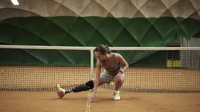 A beautiful girl stretches her legs muscles on an indoor tennis court. Disabled. Tennis net behind. Front view.  stock video footage