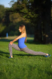 Beautiful girl stretches the legs in the park Royalty Free Stock Photo