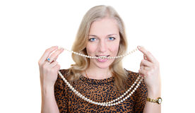 Beautiful girl   a string of pearls between her teeth Royalty Free Stock Photo