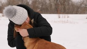 Beautiful girl strokes and feels sorry for her dog winter park. Woman kissing dog hugging Stock Photo