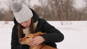Beautiful girl strokes and feels sorry for her dog winter park. Woman kissing dog hugging Royalty Free Stock Photos
