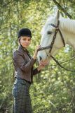 Beautiful girl stroking horse outside. Young beautiful girl stroking a horse outside Stock Photography