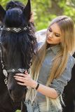 Beautiful girl stroking horse outside. Young beautiful girl stroking a horse outside Royalty Free Stock Images