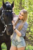 Beautiful girl stroking horse outside. Young beautiful girl stroking a horse outside Royalty Free Stock Photo
