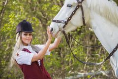 Beautiful girl stroking horse outside. Young beautiful girl stroking a horse outside Stock Photo