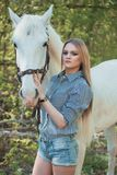 Beautiful girl stroking horse outside. Young beautiful girl stroking a horse outside Stock Images