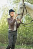 Beautiful girl stroking horse outside. Young beautiful girl stroking a horse outside Stock Image