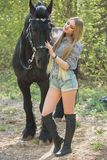 Beautiful girl stroking horse outside. Young beautiful girl stroking a horse outside Royalty Free Stock Photography