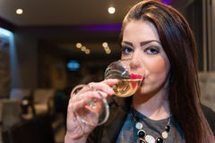 Beautiful girl with strong makeup drink white wine Stock Photos