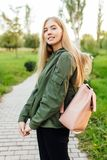 Beautiful girl student, dressed in a jacket with a briefcase, wa stock photo