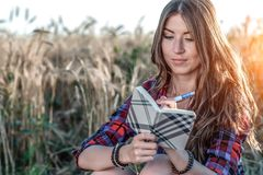 Beautiful girl student field. Journalist. Concept new ideas, summer in nature. In his hand he writes notebook, long hair Stock Photo