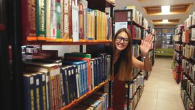 Beautiful girl student fooling around in the library stock video footage