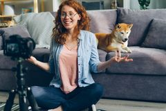Beautiful girl student recording video with dog for internet vlog at home. Sitting on floor talking and gesturing using camera on tripod. People and blogging stock photography