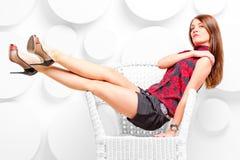 Beautiful girl in studio posing in chair Stock Photography