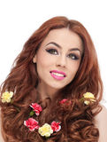 Beautiful girl in studio with yellow and red carnations in her curly hair Stock Photo