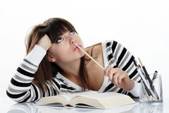Beautiful girl studying sitting at the table with books, pencil Royalty Free Stock Photos