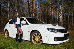 Beautiful girl and stylish white sports car. On nature Royalty Free Stock Image