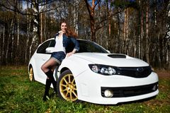 Beautiful girl and stylish white sports car Stock Photos