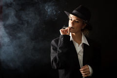 Beautiful girl in a suit, smoking Stock Image