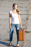 Beautiful girl with a suitcase. Outdoors shooting Stock Image