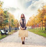Beautiful girl with a suitcase in a park Stock Images