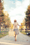 Beautiful girl with a suitcase in a park Royalty Free Stock Photography