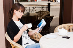 Beautiful girl in a summer cafe reading a book Royalty Free Stock Photo