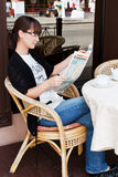 Beautiful girl in a summer cafe reading newspaper Royalty Free Stock Photos