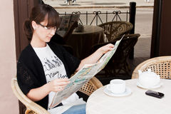 Beautiful girl in a summer cafe reading newspaper Stock Images